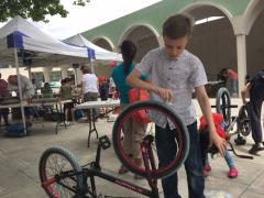 Boy chalking bike Mini Green Fair
